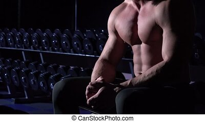 Muscular man in gym shows his muscles on his chest