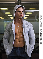 Muscular man in hood jacket at gym - Muscular young man in...