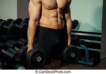 Muscular man in the gym with dumbbells