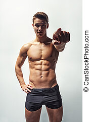 Muscular man in underwear pointing forward - Bottom view of...