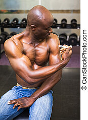 Shirtless muscular man injecting steroids in the gym