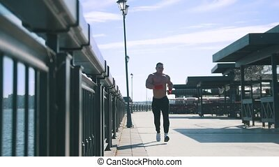 Muscular man is awkwardly jogging on the promenade at sunny day,