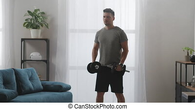 muscular man is training at home, holding dumbbells in hands and lifting, powerlifting and fitness