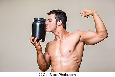 Muscular man kissing nutritional supplement - Shirtless...