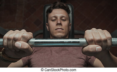 Muscular man lifting a barbell on bench at gym, top view