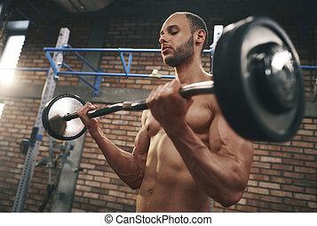 Muscular man lifting barbell in gymnasium