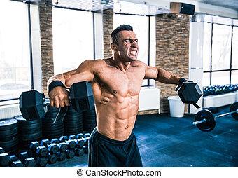 Muscular man lifting dumbbells at gym