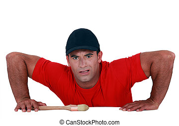 Muscular man lifting himself up onto a ledge