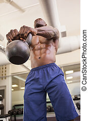 Muscular man lifting kettle bell in gym - Low angle view of ...