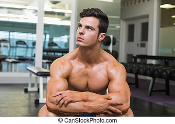 Muscular man looking away in gym