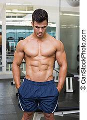 Muscular man looking down - Shirtless muscular man looking...