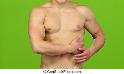 Muscular man make massage on left side. Green screen,...