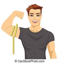 muscular man measuring biceps with tape measure