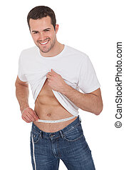 Muscular man measuring waist - Muscular young man measuring...
