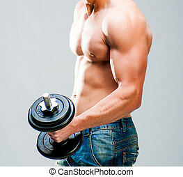 muscular man - Muscular man with dumbbells on a gray...