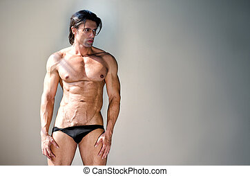 Muscular man nearly naked in underwear looking to a side