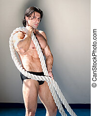Muscular man nude with heavy, big rope in his arms