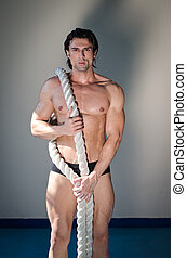 Muscular man nude with heavy, big rope on one shoulder