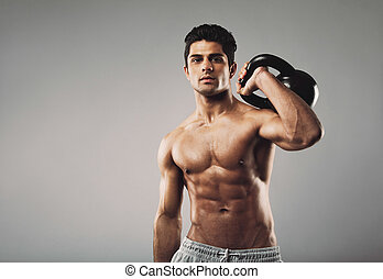 Muscular man performing crossfit workout with kettlebell -...