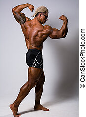 Muscular man posing against a light background