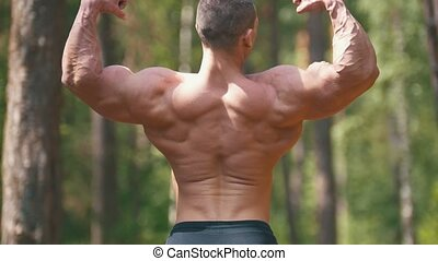 Muscular man posing bodybuilding in the summer forest - huge biceps