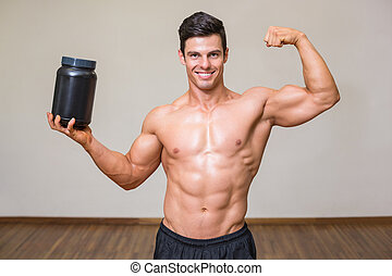 Muscular man posing with nutritional supplement in gym - ...