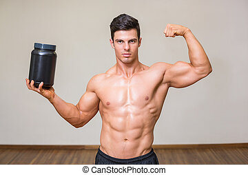 Muscular man posing with nutritional supplement in gym -...