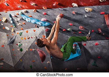 man practicing rock-climbing on a rock wall indoors