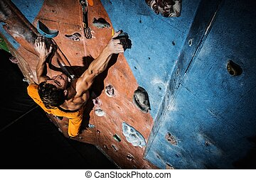 Muscular man practicing rock-climbing on a rock wall indoors