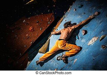 Muscular man practicing rock-climbing on a rock wall indoors...
