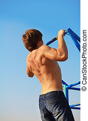 Muscular man pull oneself up over blue sky