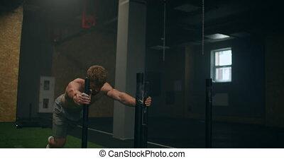 Muscular man pushing sled at gym during exercise slow motion
