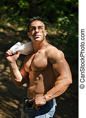 Muscular man shirtless in jeans outdoors under trees