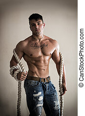 Muscular man shirtless with heavy, big rope - Muscular young...