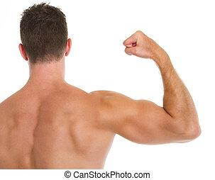 Muscular man showing biceps. Rear view