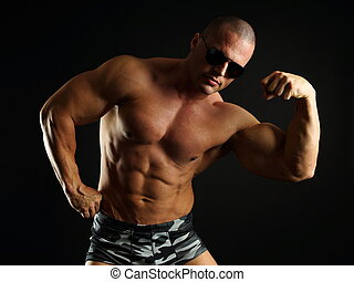 Muscular man shows biceps