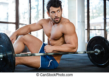 Muscular man sitting on the floor with barbell