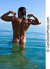 Muscular man - Muscular handsome man relaxing in the sea and...