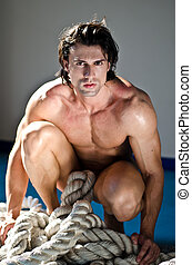 Muscular man totally naked kneeling with heavy, big rope in front of him