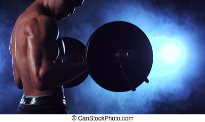 Muscular man training biceps with a barbell. Black smoke...