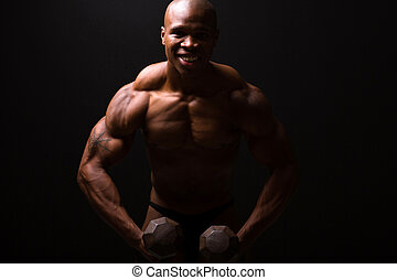 muscular man training with dumbbells