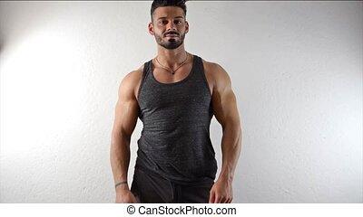 Muscular man undressing, lifting tank-top