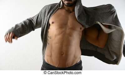 Muscular man undressing, taking off jacket