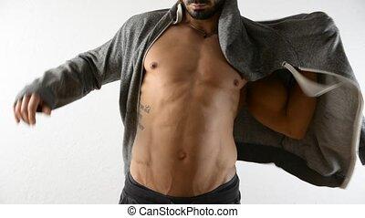 Muscular man undressing, taking off jacket