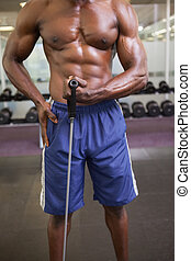 Muscular man using resistance band in gym