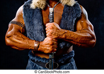 Muscular man warrior with a sword. black background