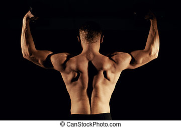 Muscular man with a dumbbell dark background