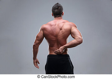 Muscular man with back pain on a gray background