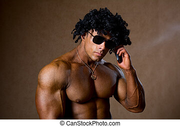 Muscular man with curly hair talking on a cell phone.