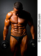 muscular man with dumbbells on black